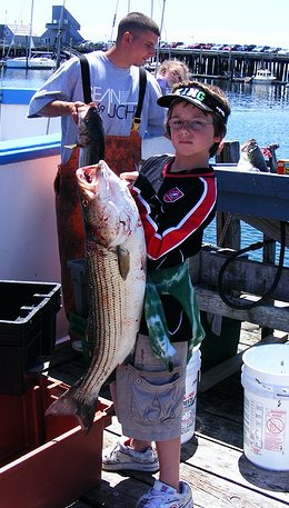Big Striped Bass Caught By A Boy Fisherman Showing Off His Catch