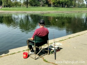 An Old Man Fishing At A Pond