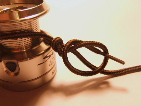 Two overhand knots to make an arbor knot fit securely to the spool of the fishing reel.