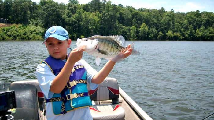 Big white crappie caught by kid on a boat.