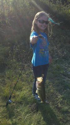 Happy Girl with a Largemouth Bass Caught from a Local Pond