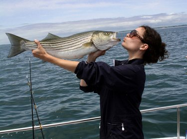 pretty Woman Kissing A Striped Bass - photo credit by cmeleskiiii