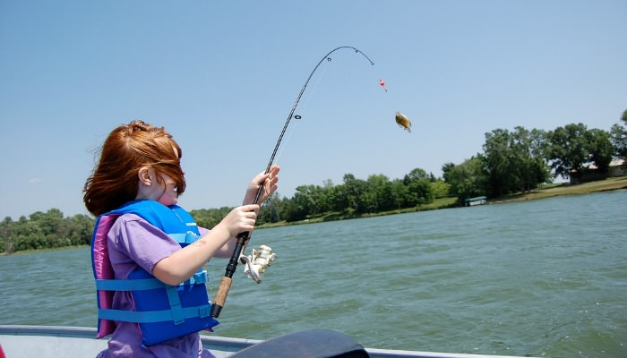 Little girl catching a crappie with small fishing pole.