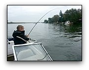 Kid fishing on a boat, beginner child catching fish in a coat jacket, cold weather.